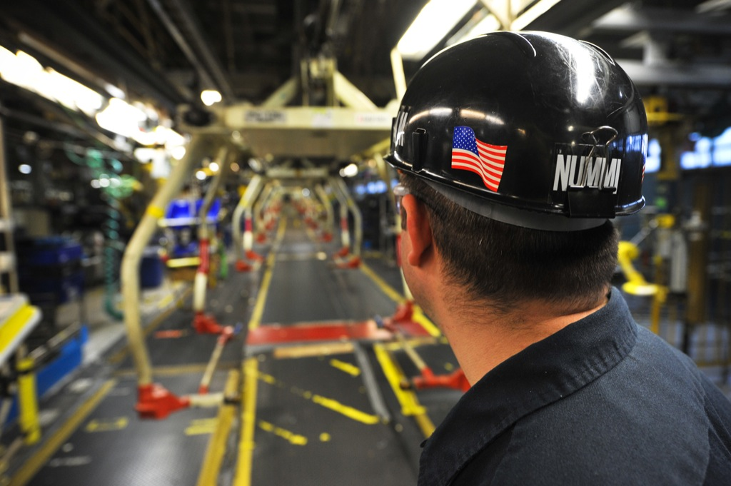 The American flag adorns the hardhat of an assembly line worker at the NUMMI plant in Fremont, CA., a joint-venture between GM and Toyota that produced cars for both companies. Image Source: NUMMI